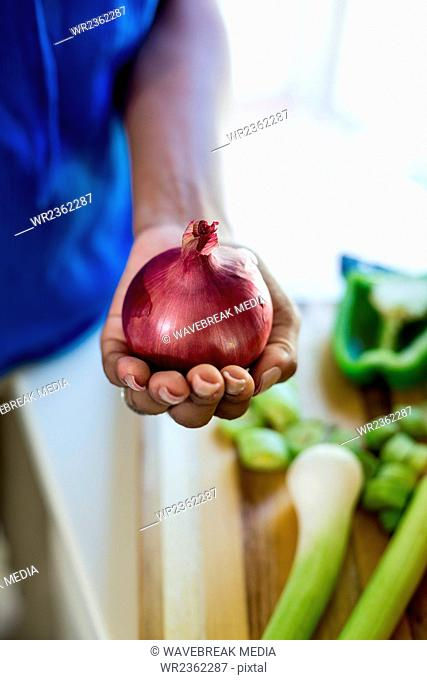 Mid-section of woman holding onion in hand