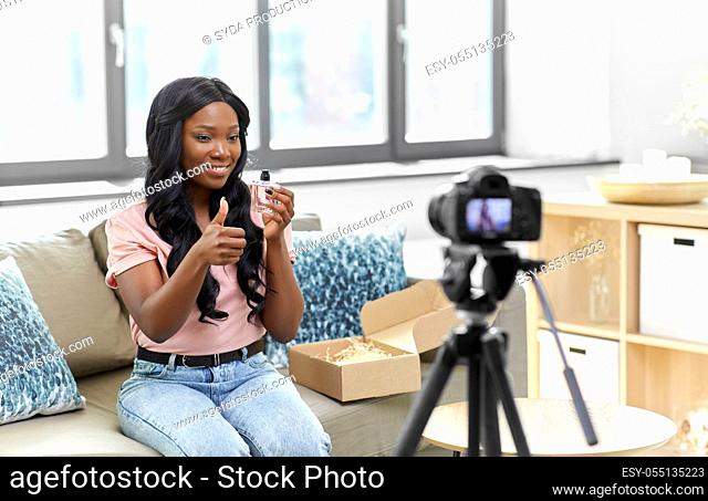 female beauty blogger with camera and perfume