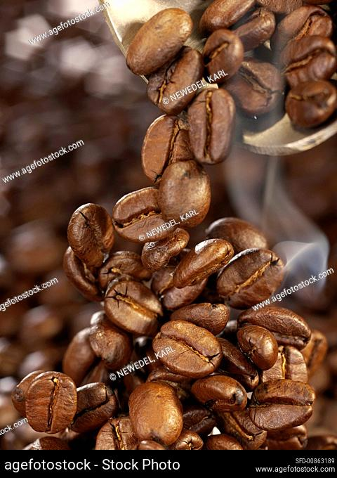 Freshly roasted coffee beans falling onto a heap