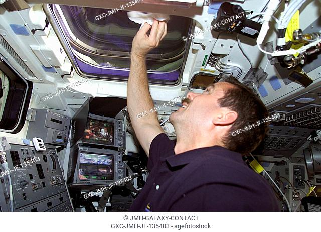 Astronaut Chris A. Hadfield of the Canadian Space Agency (CSA) wipes clean one of the overhead windows on the aft flight deck of the Space Shuttle Endeavour as...