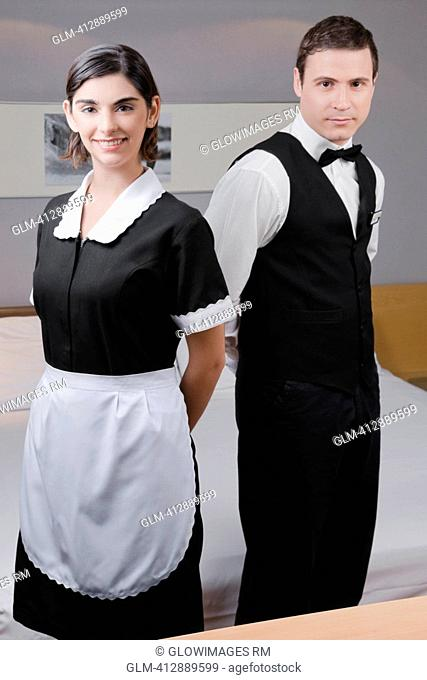 Portrait of a waiter and a waitress standing in a hotel room