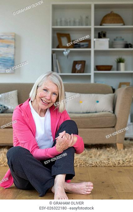 Senior woman sitting on the floor. She is smiling and looking at the camera