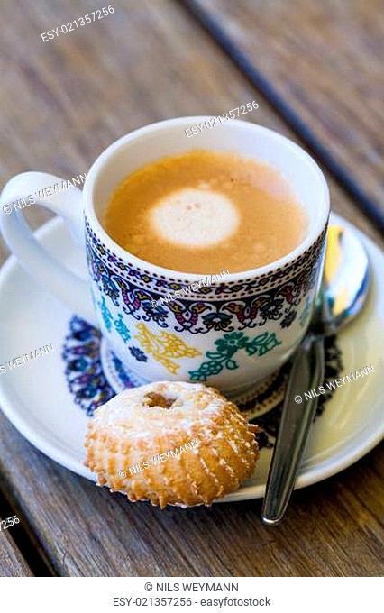 Tasse mit frischem Kaffe Espresso Kaffeelöffel und Feingebäck