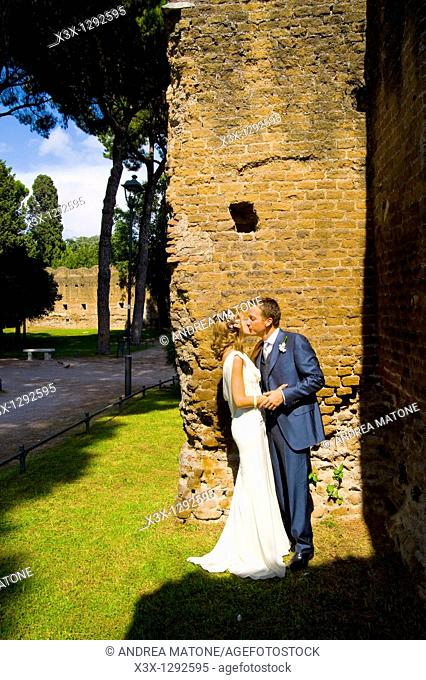 Young bride and groom kissing near stone wall