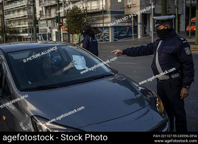 07 November 2020, Greece, Athen: Policemen with nose-mouth coverings check the papers of a driver and the permission of the passengers to move around the city