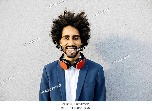 Portrait of smiling young businessman with headphones at a wall