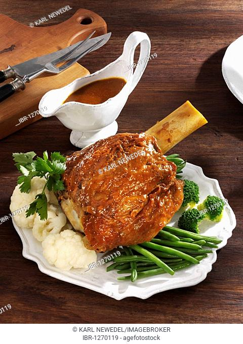 Braised veal shank with green beans, broccoli, cauliflower and parsley served on a platter with a gravy boat on a wooden table