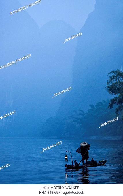 Silhouette of a cormorant fisherman paddling a lantern lit bamboo raft at dawn on the Li River, China, Asia