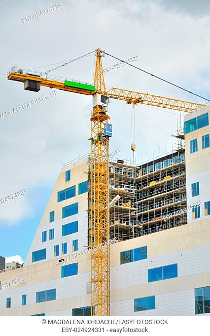 Working crane on a modern office building under construction