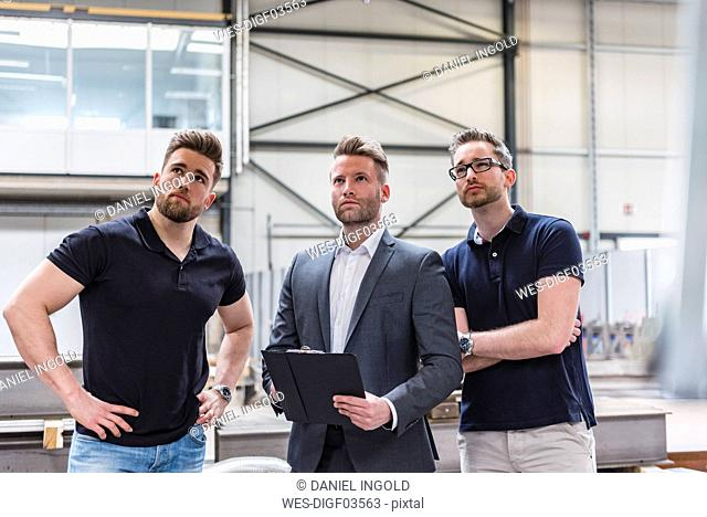 Three men on factory shop floor looking around