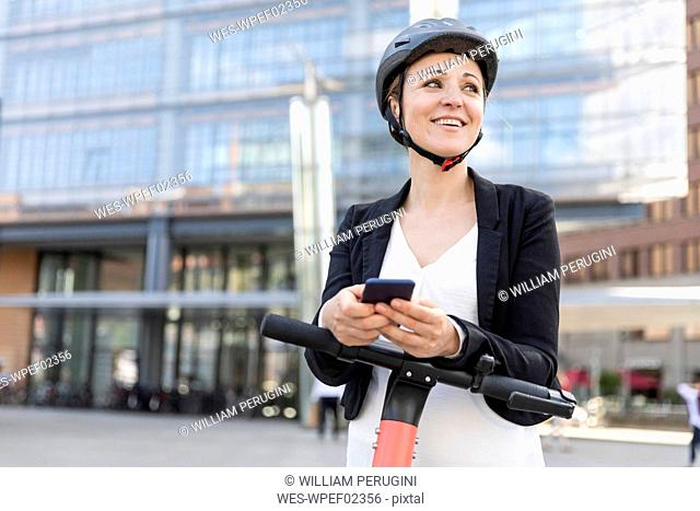 Happy woman with e-scooter and smartphone in the city, Berlin, Germany
