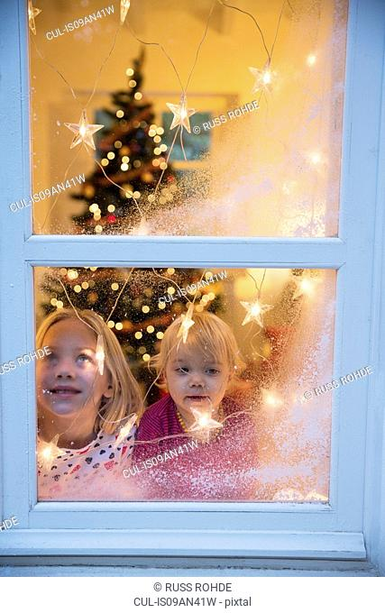 Sisters looking out of window with Christmas decorations