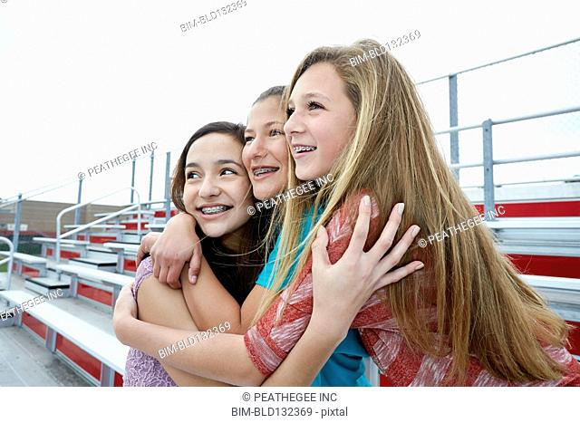 Teenage girls hugging on bleachers