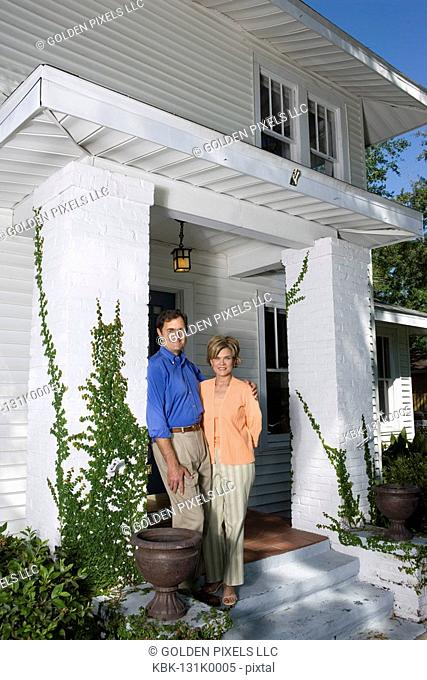 Portrait of a mature couple standing outside a house