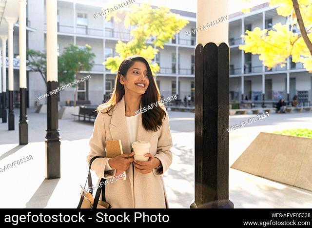 Smiling young woman with book and takeaway coffee on the go in the city