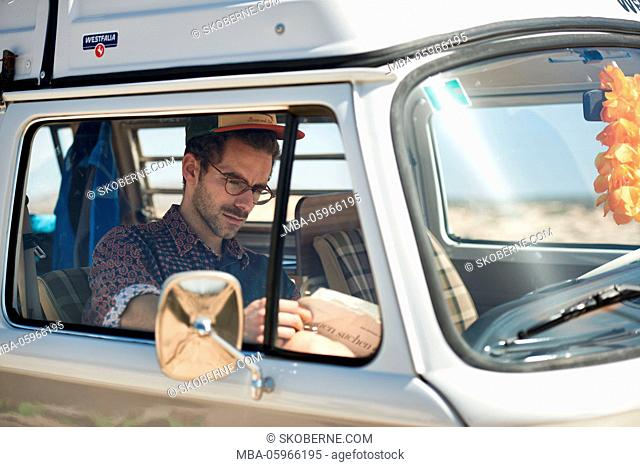 young man sits readingly in old camper