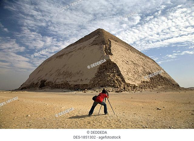 A man taking a picture of a Pyramid