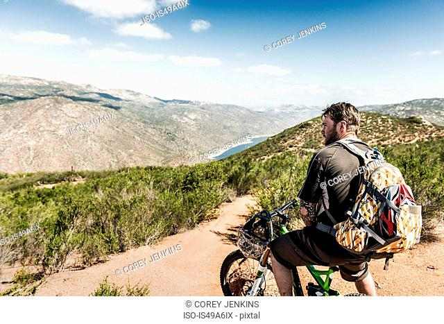 Downhill mountain biker looking at view