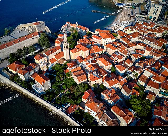 Majestic sunny cityscape of old town of Budva in Montenegro. There is Saint Ivan and Holy Trinity churches, old houses with shingled red-orange roofs