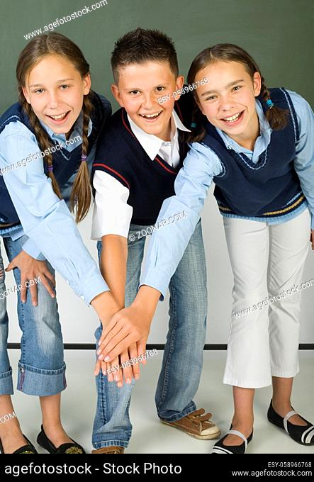 Two, young girls and one boy standing with handshake in front of blackboard. Smiling and looking at camera. Front view