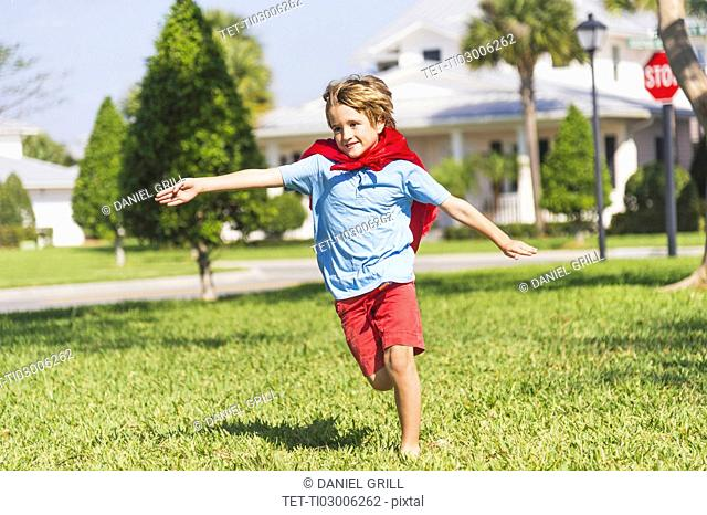 Boy (8-9) running with cape
