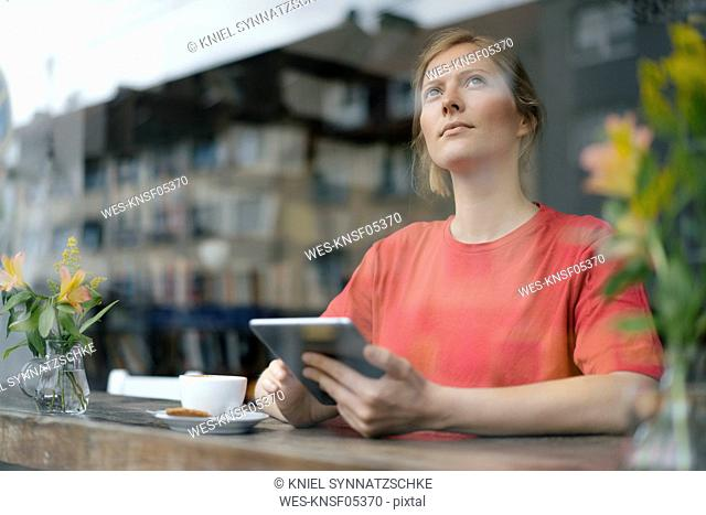 Young woman using tablet at the window in a cafe
