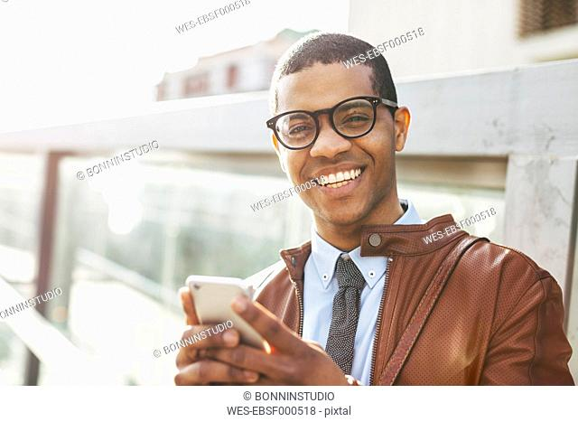 Portrait of smiling businessman with smartphone wearing leather jacket and glasses