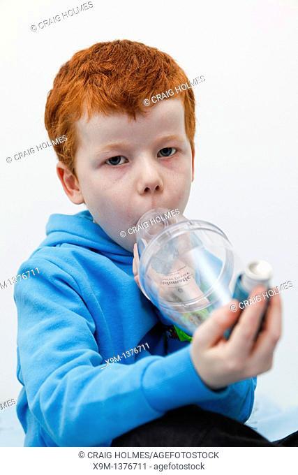 Little boy using his asthma inhaler to alleviate symptoms