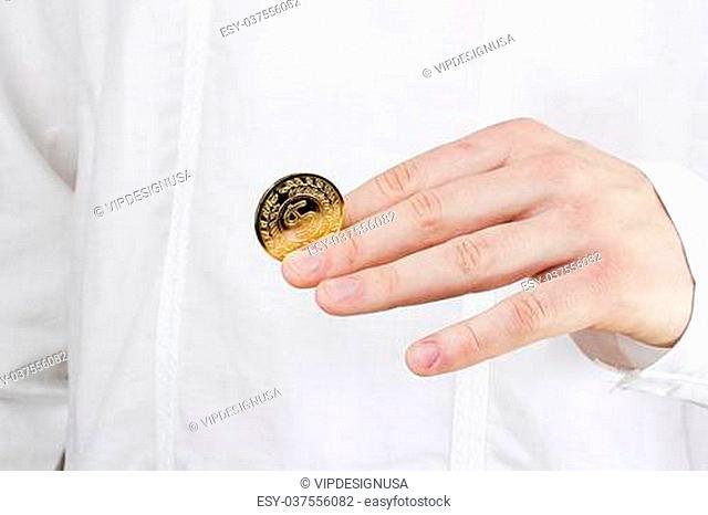 Close-up photograph of a golden coin between a man's fingers