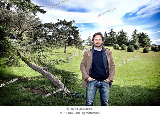Man standing beside a tree in a park. Green Economy. Rome (Italy), November 2013