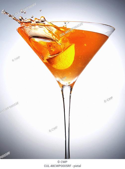 Fruit splashing in cocktail glass