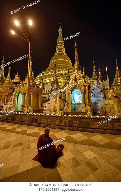 Monk meditating under candles at Shwedagon Paya, the holiest site in Yangon, Myanmar