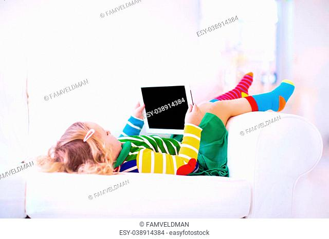 Funny little toddler girl with tablet pc relaxing on a white couch