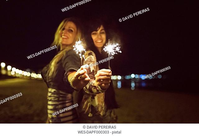 Two happy friends holding sparklers on the beach at night