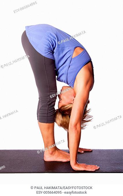 Beautiful healthy woman doing Standing Forward Fold Uttanasana hamstring stretch yoga, on white