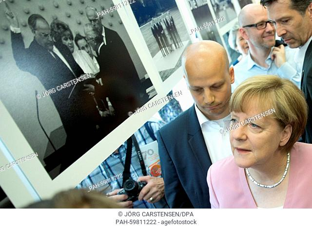 German Chancellor Angela Merkel (CDU) looks around a photo gallery during an open day at the Konrad-Adenauer-Haus in Berlin, Germany, 4 July 2015