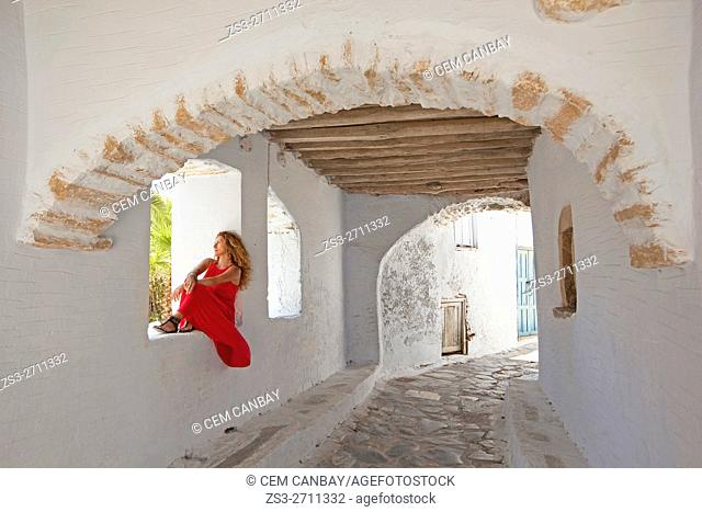 Woman in an archway in the old town Chora, Amorgos, Cyclades Islands, Greek Islands, Greece, Europe