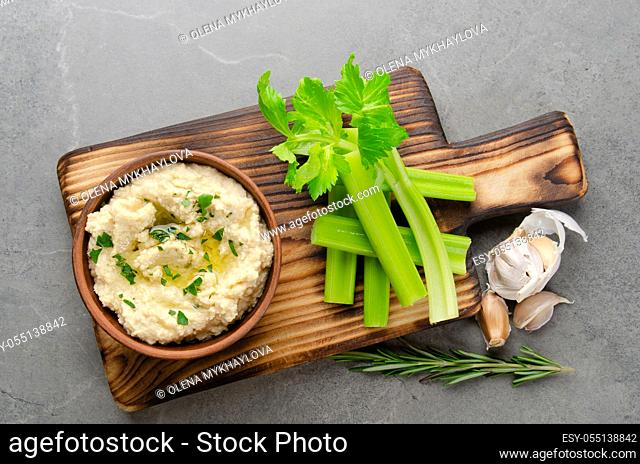 Flat lay view at vegetable Hummus dip dish topped with olive oil served with celery slices