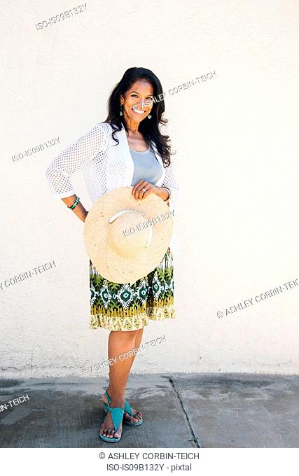 Portrait of senior woman, outdoors, holding sun hat, smiling