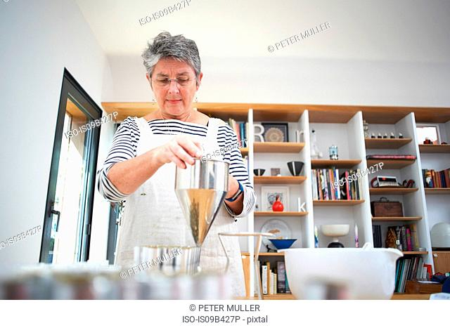 Senior woman in kitchen, using pancake funnel to dispense cream, homemade cosmetics, into pots, mid section