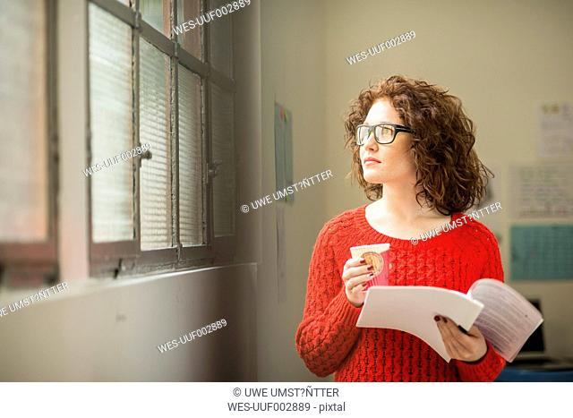 Young woman with document and coffee to go at the window