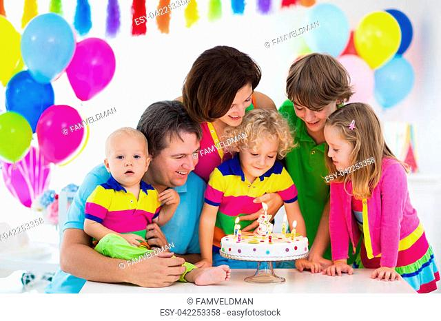 Family celebrating kids birthday. Parents and children celebrate together. Child party with balloon decoration, cake, candles and presents