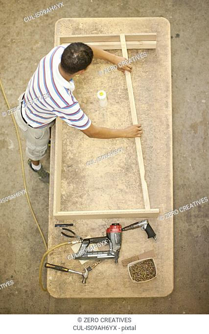 Upholsterer constructing a wooden frame on table