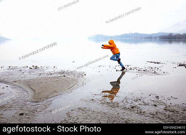child runs by the lake