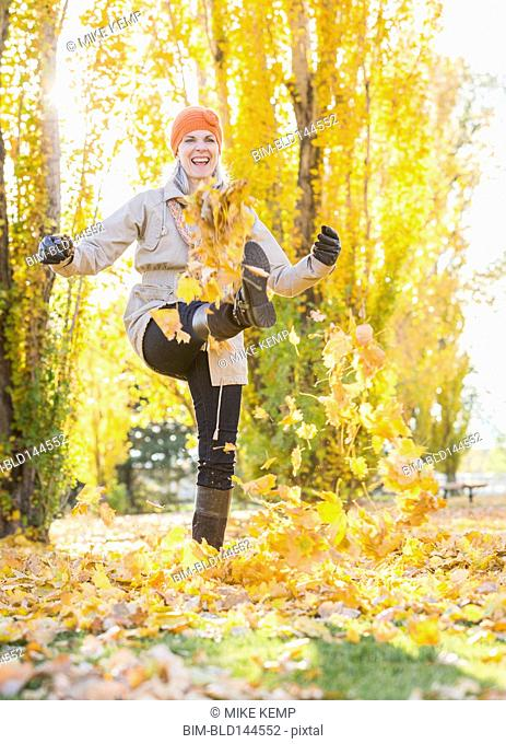 Older Caucasian woman kicking autumn leaves