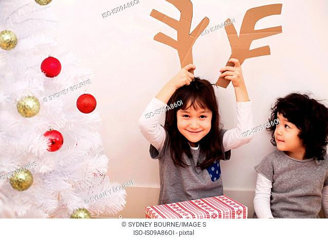 Two girls preparing for Christmas, playing with cardboard reindeer antlers