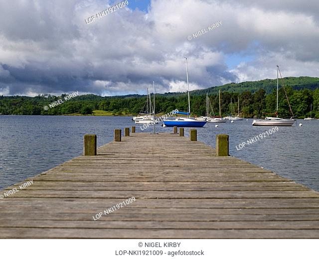 England, Cumbria, Ambleside. View along a wooden jetty towards boats moored on Lake Windermere at Waterhead