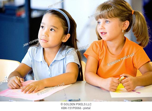 Two little girls coloring together