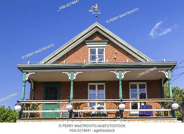 Second story balcony of an old 1900s red brick cottage style house with white and green trim plus decorated wooden posts, Quebec, Canada