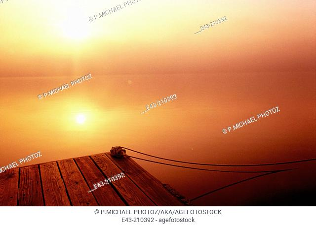 Lake covered with mist at sunrise with the sun cutting through the mist and a boat dock with rope, Pennsylvania. USA